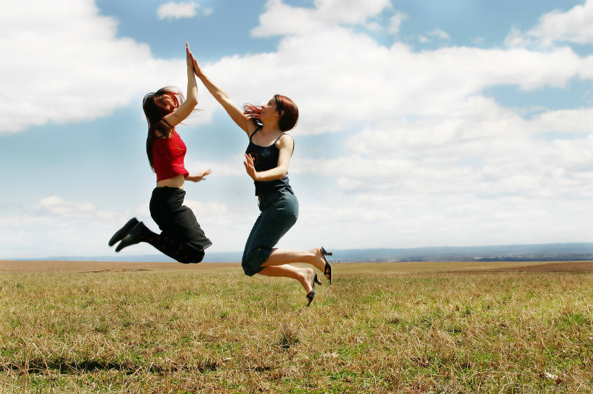 friends jumping and clapping hands in the air